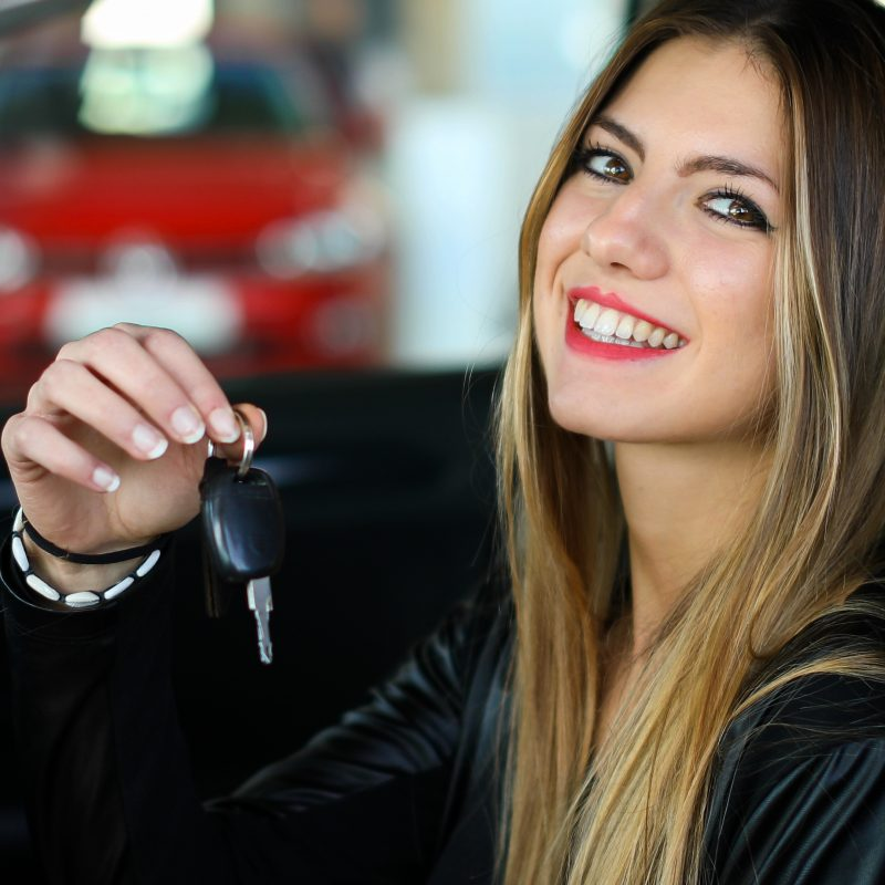 Young woman showing her new car keys